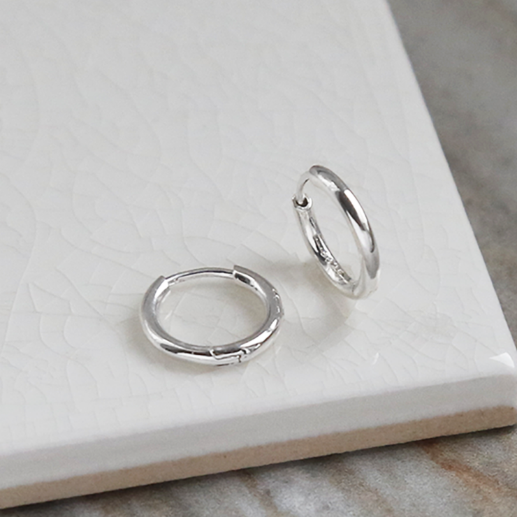 big sterling silver huggies on white background.