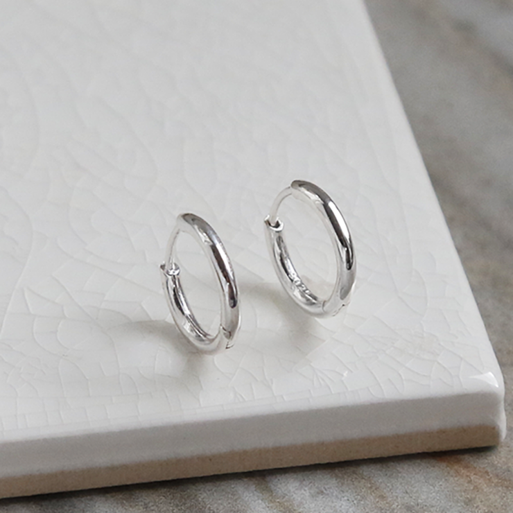 Big polished sterling silver huggies on white background.