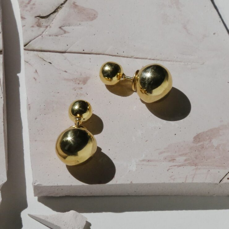 Gold Plated Venus Stud Earrings with a tile background