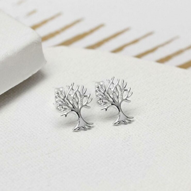 Silver Tree stud earrings on white ceramic background with gold detail paper
