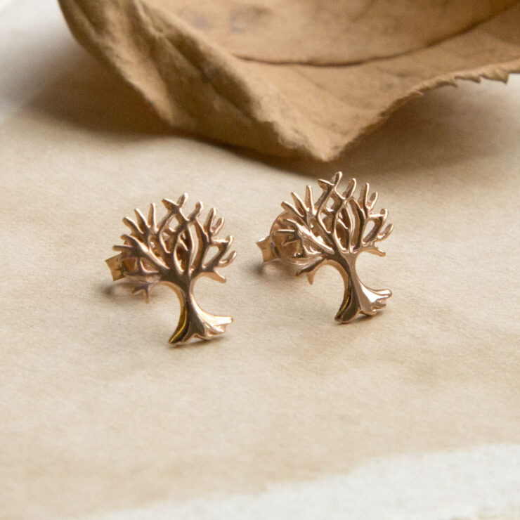 Rose Gold Tree studs on warm tone paper with autumn leaves in background