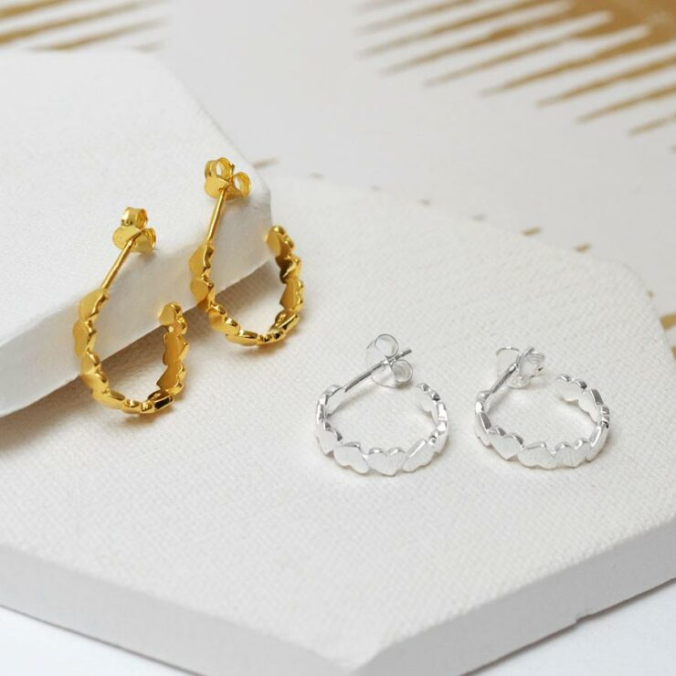 Gold and silver love hoops together on white ceramic tiles with gold detail background