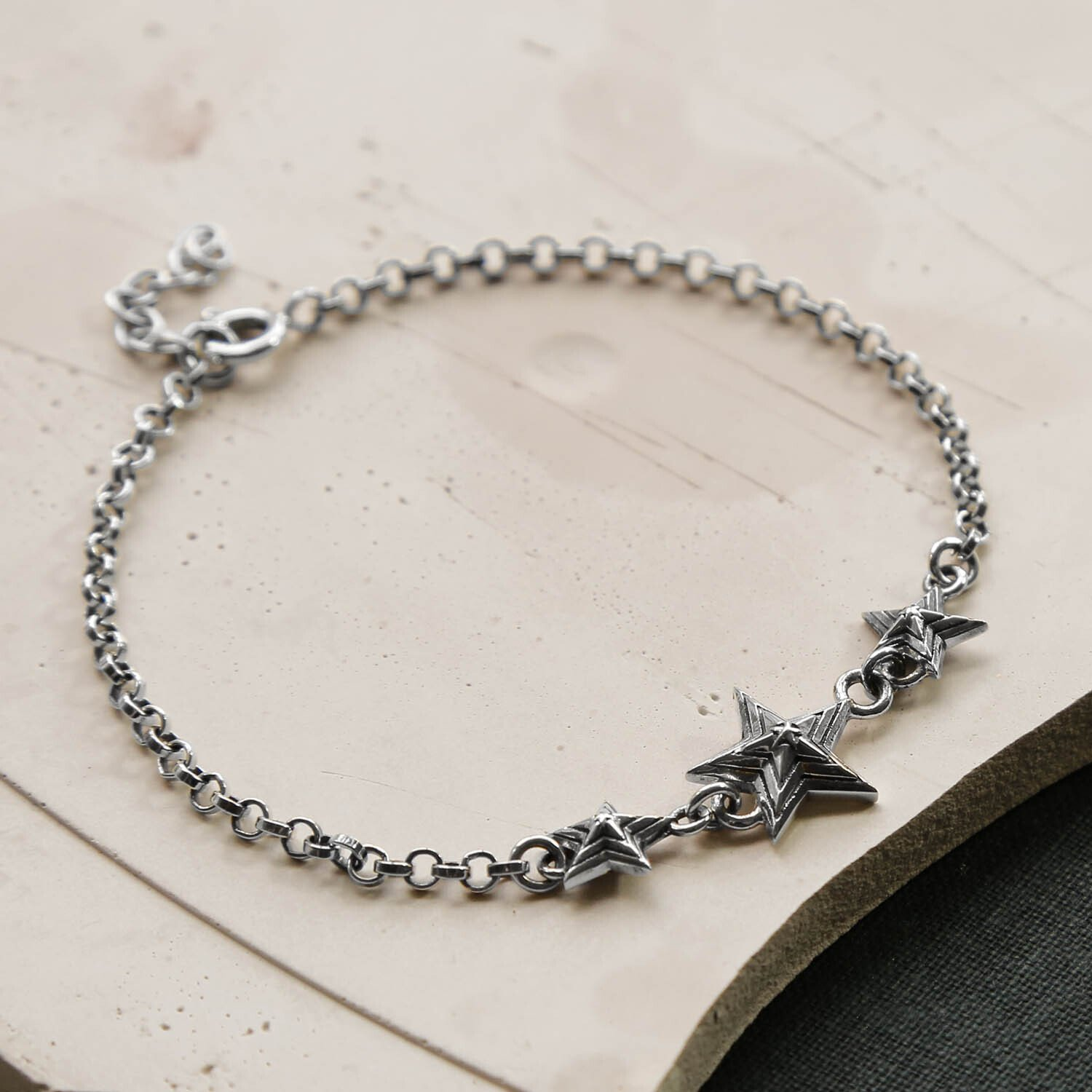 Oxidised Silver Chain Bracelet with 3 Silver Oxidised Stars on a creamy, pastel Plaster Background