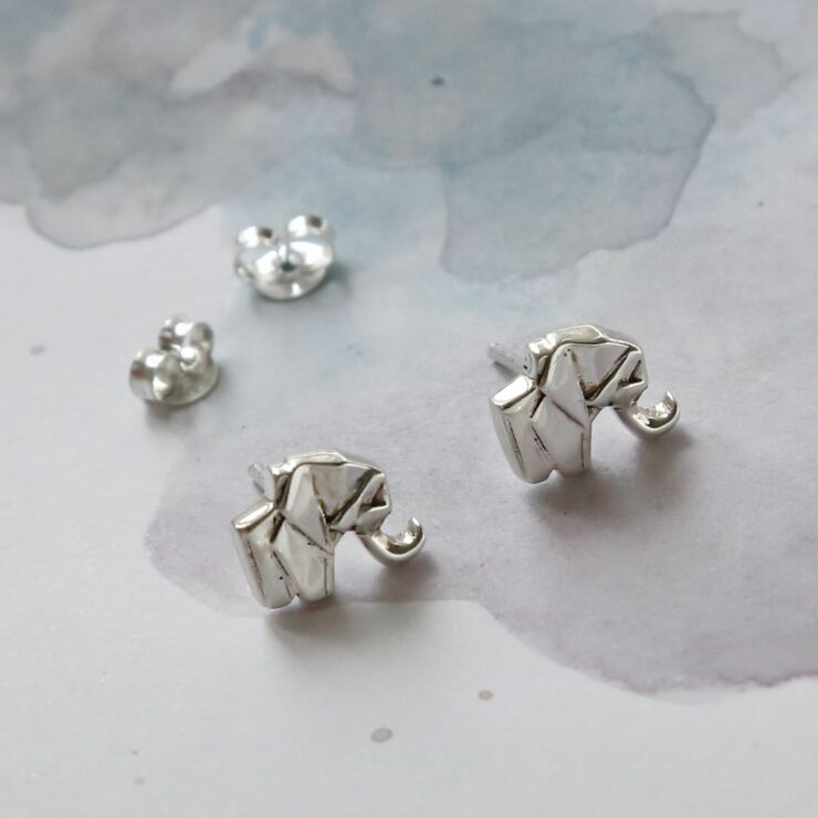 Two silver geometric elephant stud earrings sat on a white and blue water colour background with two silver butterfly backs in the background