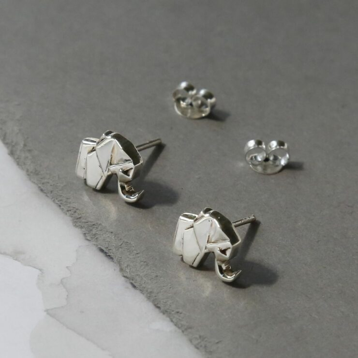 Two silver geometric elephant stud earrings sat on a grey slate coloured material with two silver butterfly backs in the background
