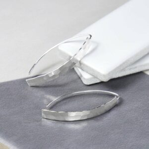 Hammered style Earrings placed on grey and white tiles
