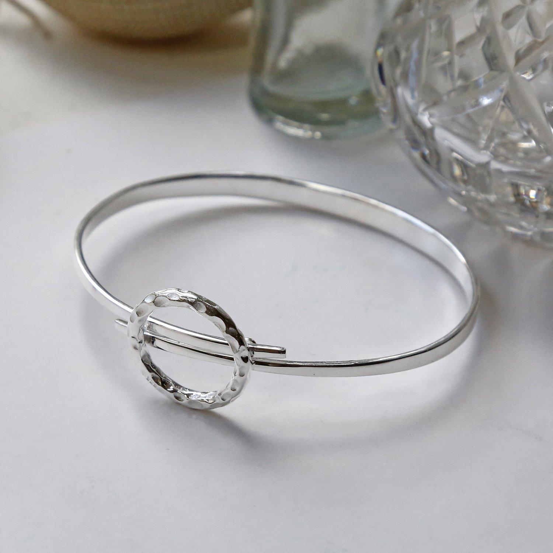 sterling silver joyful wreath bangle on side with crystal vase