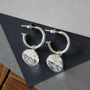 Sterling Silver  Disc Stud Hoops on dark grey triangle. Hammered disc catching light