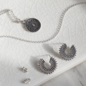 Set of oxidised sterling silver Marrakech studs and necklace on white background with butterfly fastening.