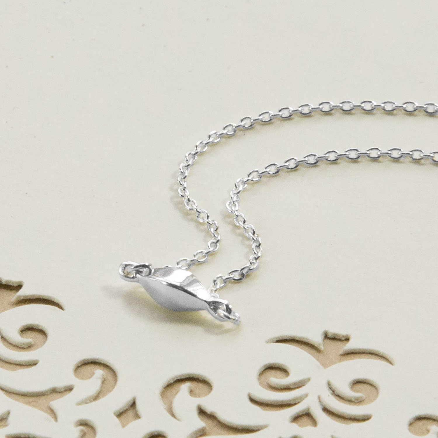 Delicate rhombus pendant on a very fine silver chain on a white background