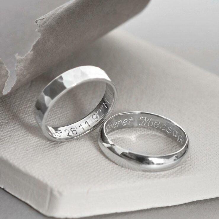 A pair of sterling silver friendship rings. One sterling silver hammered friendship ring and one polished friendship ring showing engravings.