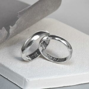A pair of sterling silver friendship rings on white paper.