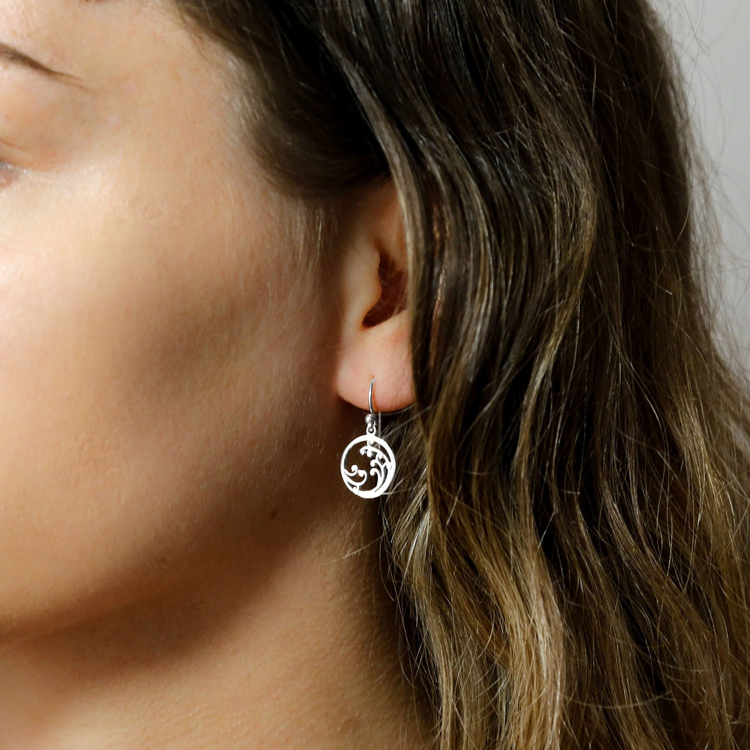 Silver drop earrings with wave details on model