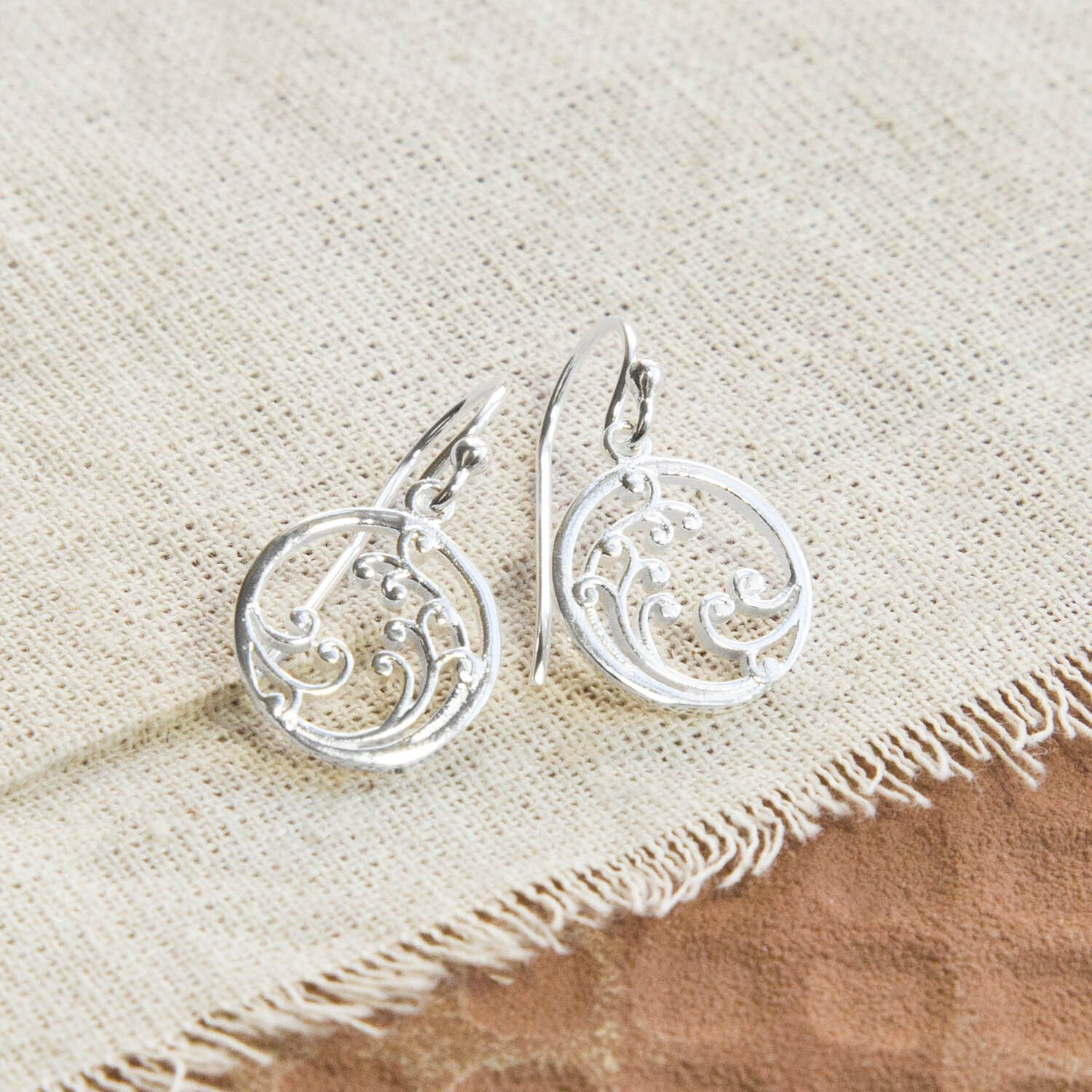 Silver drop earrings with wave details, laid out on a canvas background with terracotta tile