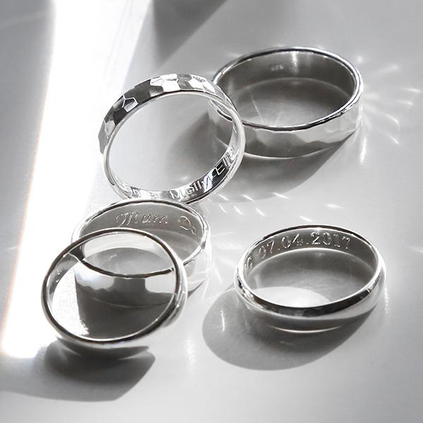 Silver Affirmation rings in different styles including Hammered and Polished finish, on plain whte background with Shadow and light bursts