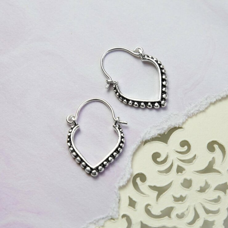 Oxidised and Silver Hoops with Circular detail resting on a purple waterclour background layered on top of cut out pattern paper