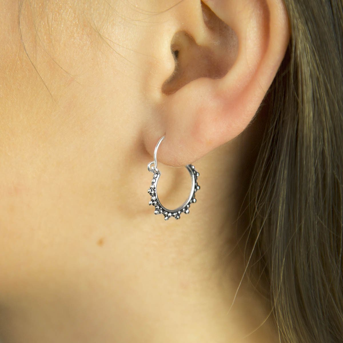 Silver and Oxidised Hoops with circular ball detail pattern on Brunette Model