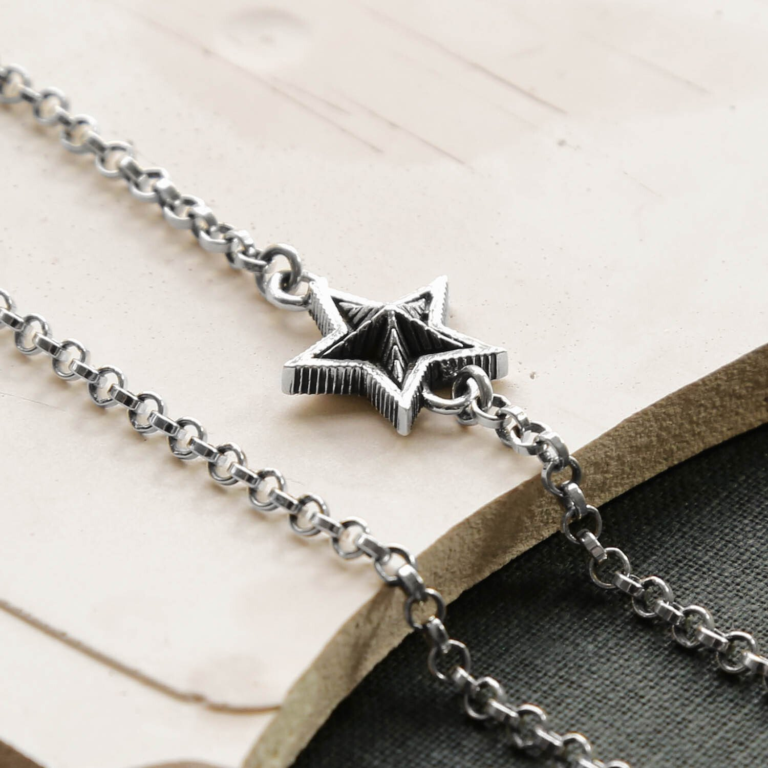 Close up Oxidised Silver Chain Necklace with A Silver Oxidised Stars on a creamy, pastel Plaster Background