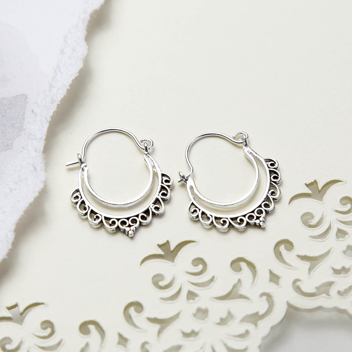 Sterling Silver Persian Waves Hoops on cream paper with ripped and pattern detail