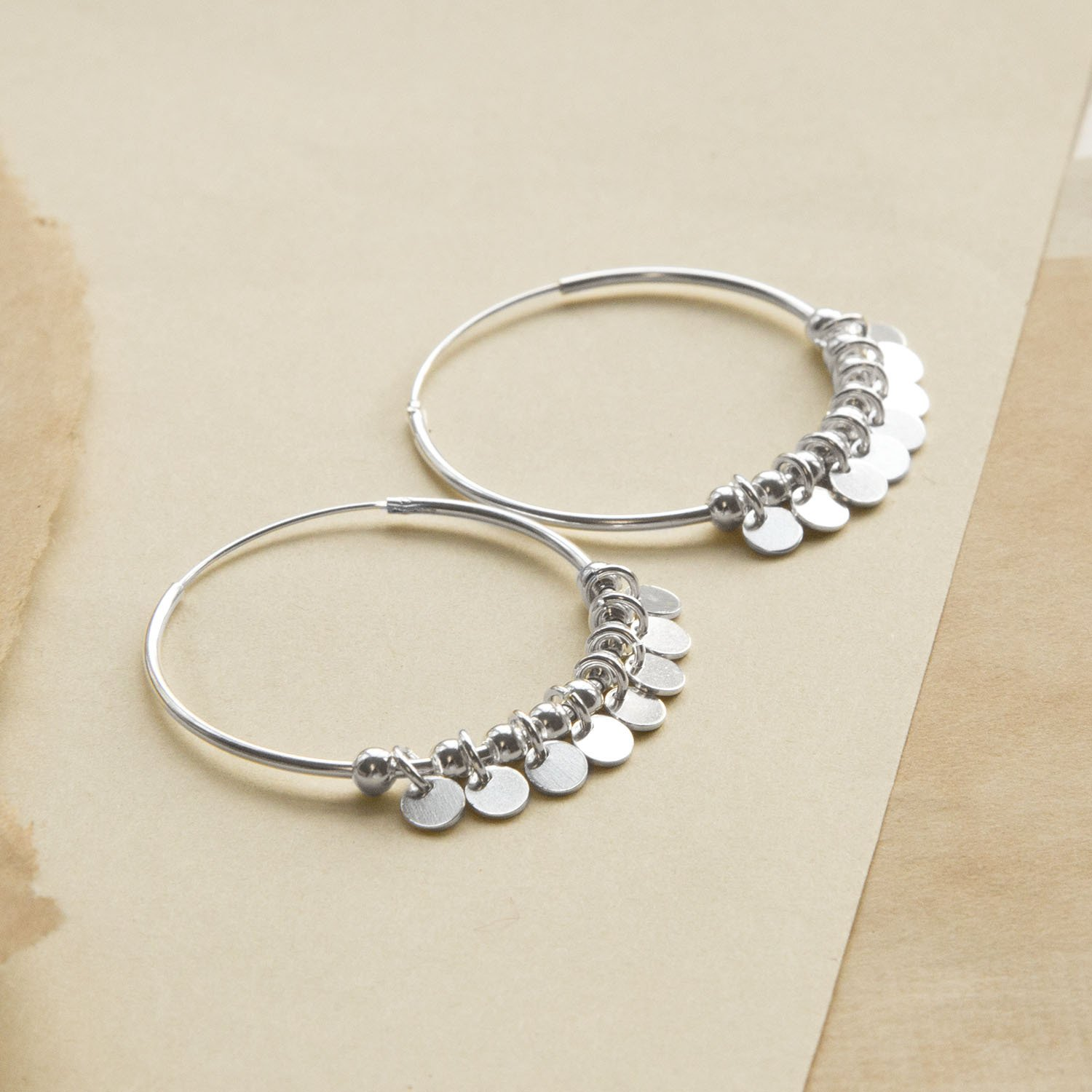 Silver Hoops with sequin detail on different coloured sandy paper background