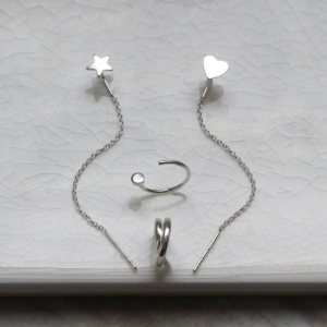 Sterling silver curated ear earring pack containing four earrings. On white background.