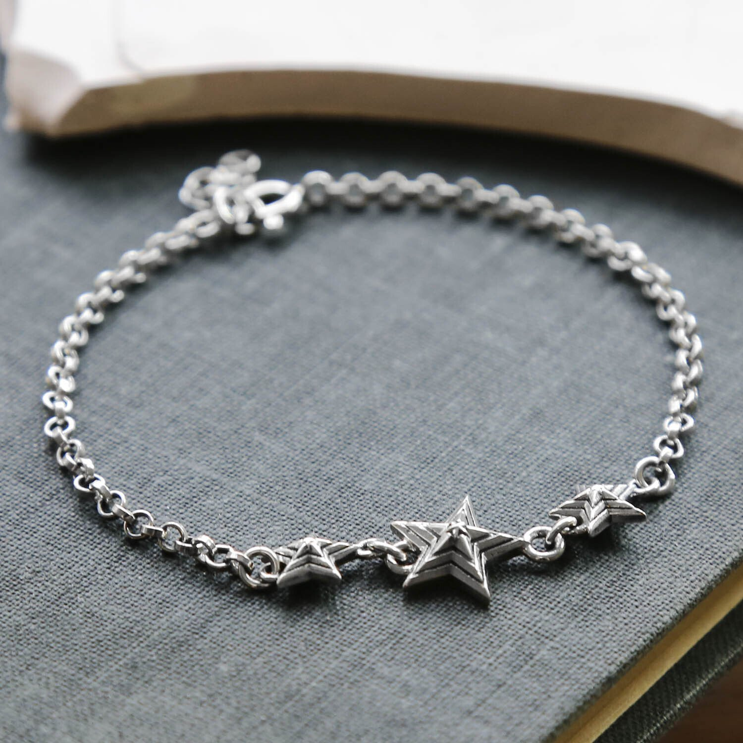 Oxidised Silver Chain Bracelet with 3 Silver Oxidised Stars on a blue textured Book Cover