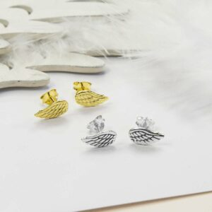 Gold Angel Wing Studs on the left and Silver Angel Wing studs on the right with Wooden wing props and white feathers in the background