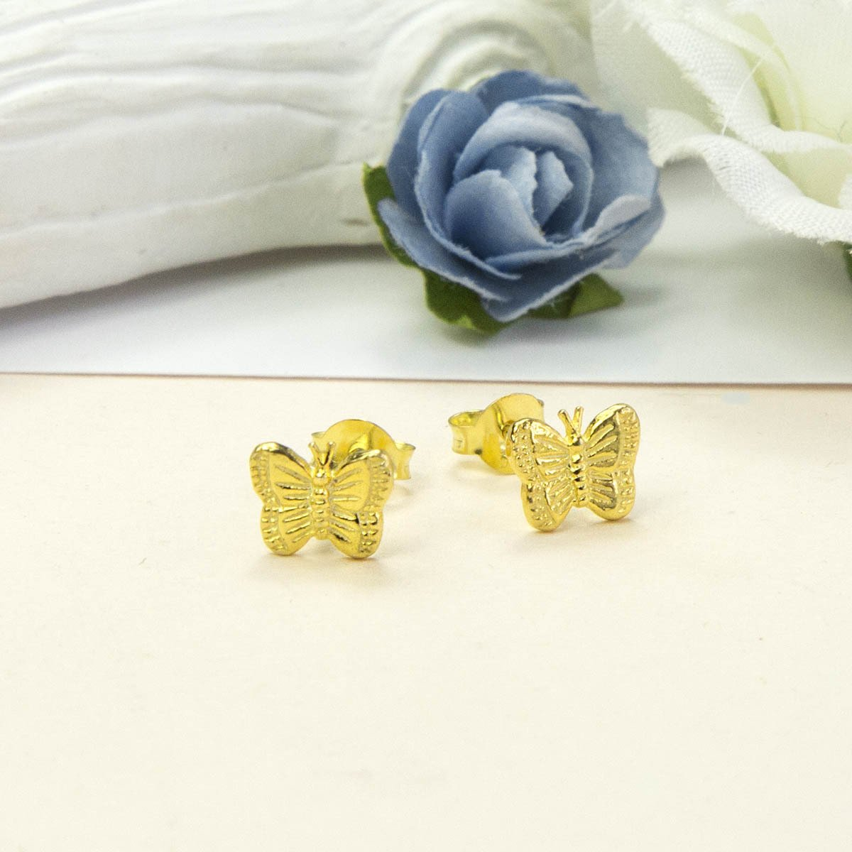 Small Gold Butterfly studs with Blue and white roses in the background
