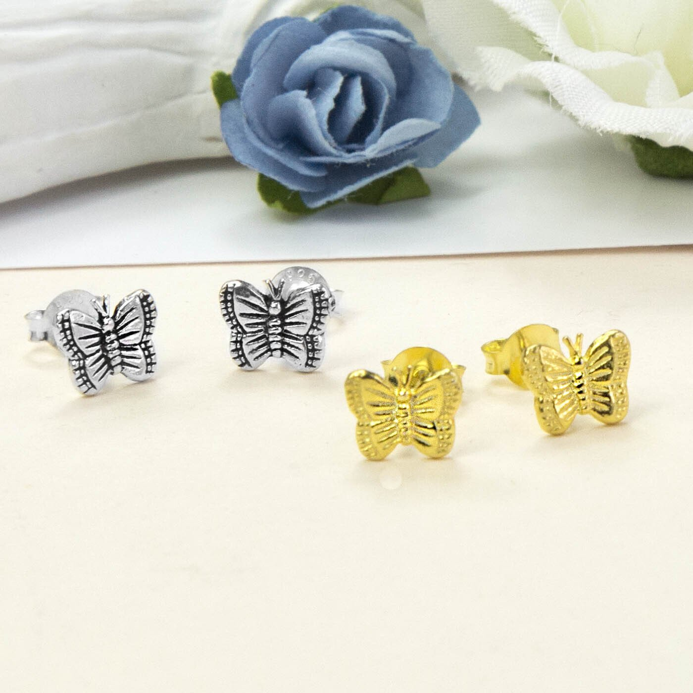 Small Silver Butterfly studs on the left and Small Gold Butterfly studs on the right with Blue and white roses in the background