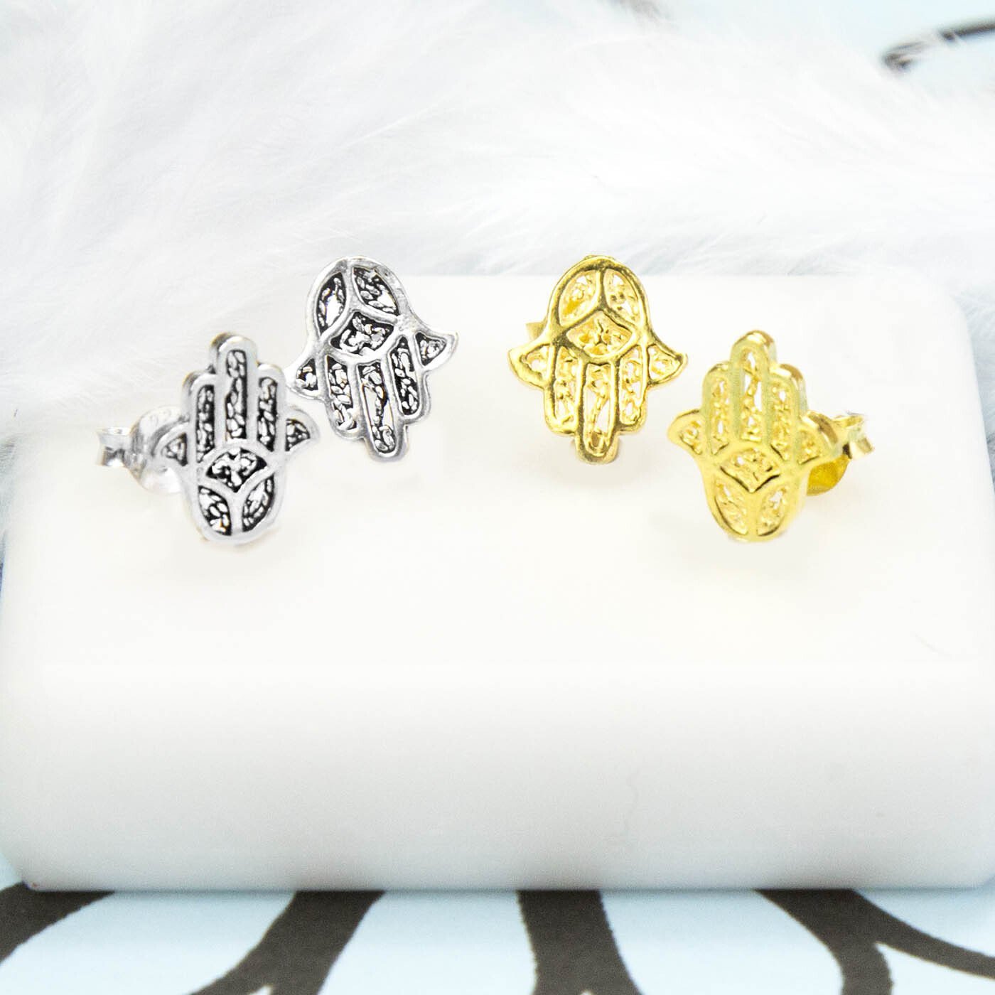 Pair of Silver Hamsa Hand Stud next to a Pair of Gold Hamsa Hand Studs on white tile background and blue and black pattern paper
