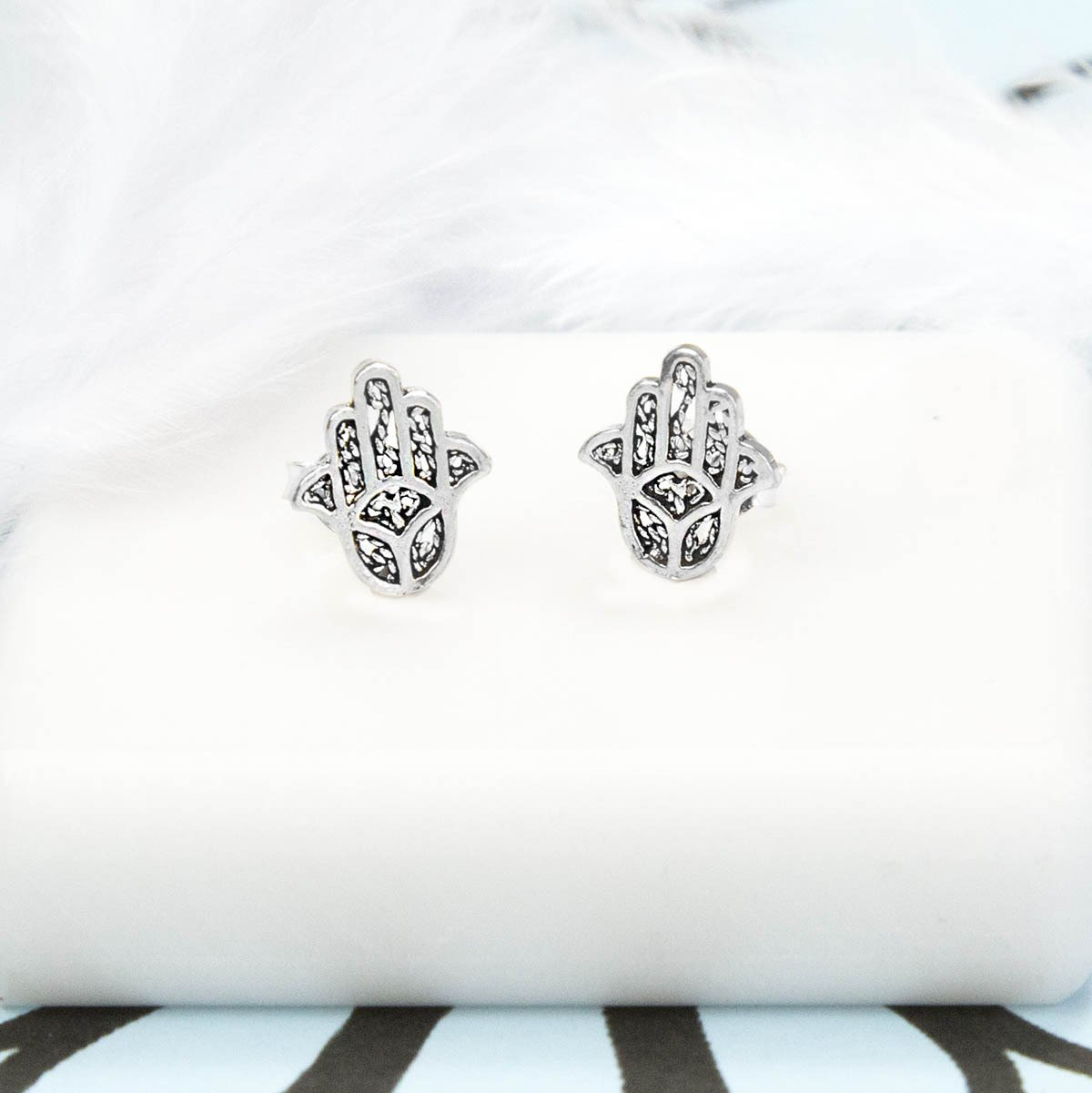 Pair of Silver Hamsa Hand Studs on white tile background and blue and black pattern paper with White Feather