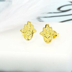 Pair of Gold Hamsa Hand Studs on white tile background and blue and black pattern paper with White Feather