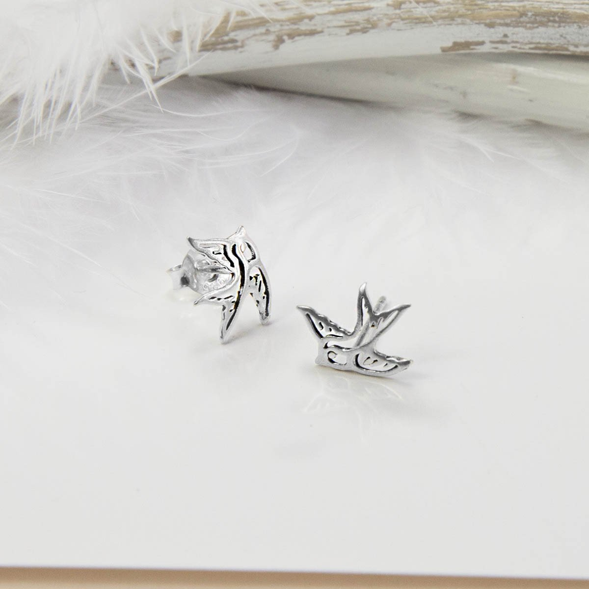 Small Silver Swallow Bird studs with white feather background