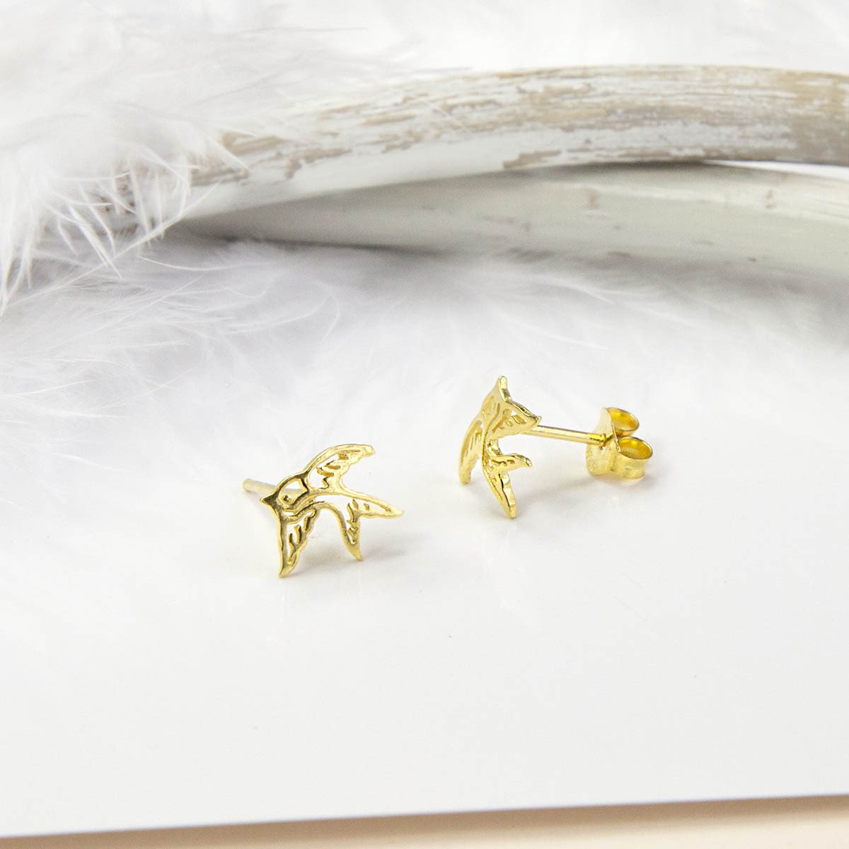 Small Gold Swallow Bird studs with white feather background