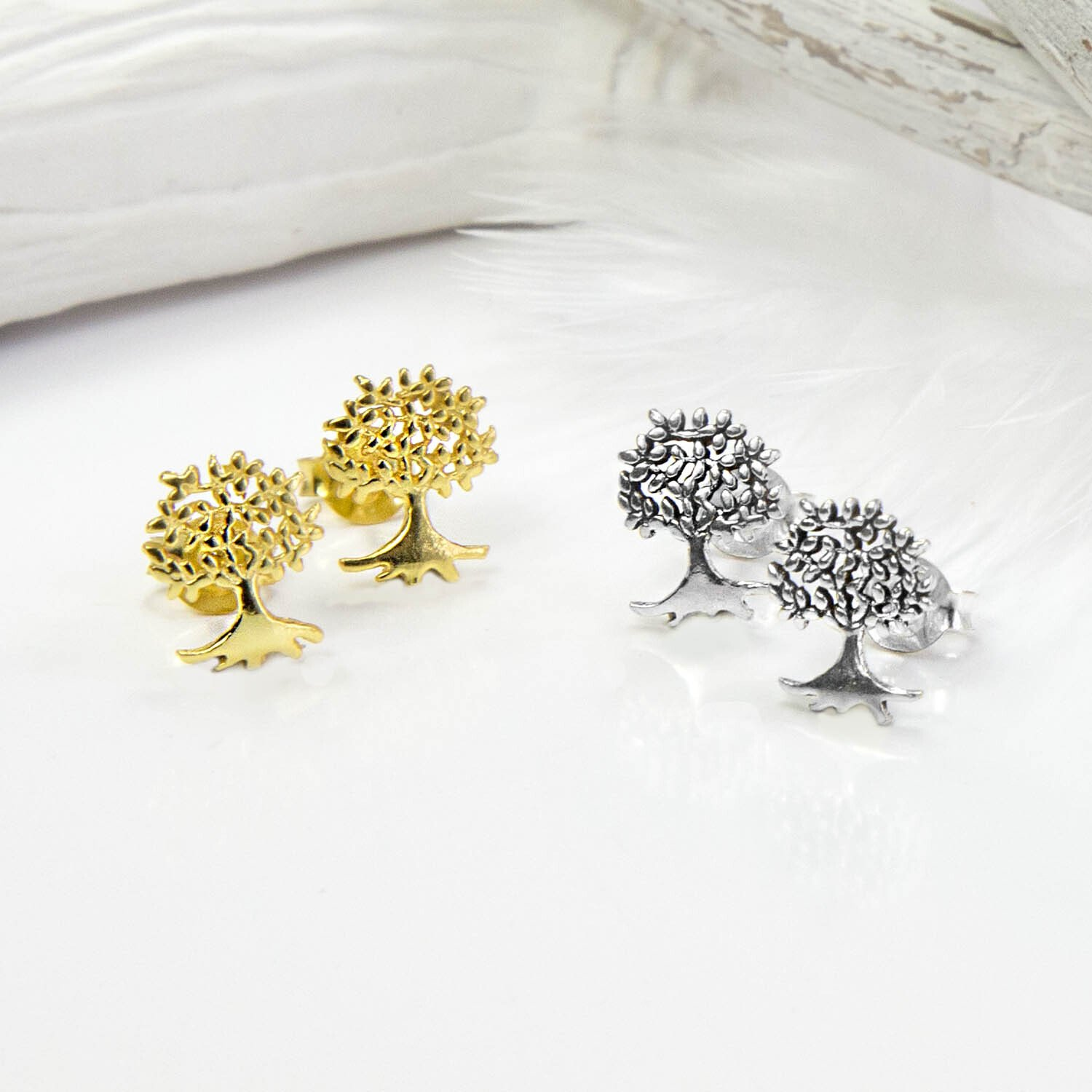Small Gold Tree studs on the left and Silver Tree studs on the right, with white feathers and background