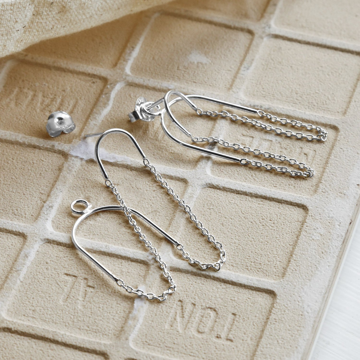 Two way chain Sterling Silver studs, one earring appearing undone on Sandy tile background with canvas