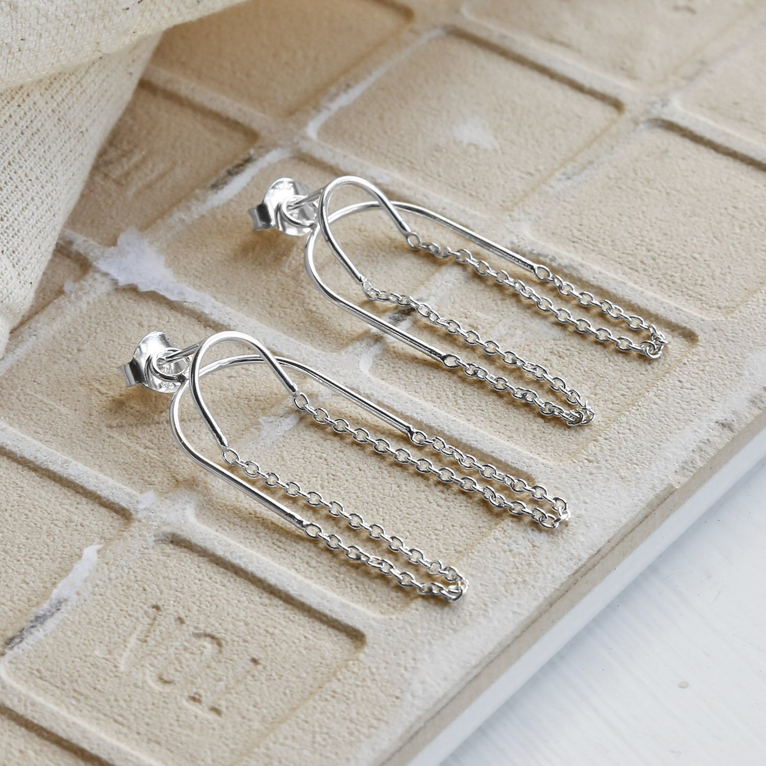 Two way chain Sterling Silver studs on Sandy tile background with canvas