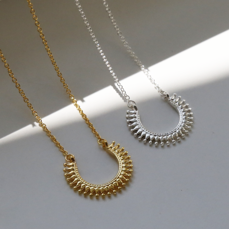 Gold plated sterling silver and sterling silver Marrakech horseshoe necklace shown together on white background with light on them.