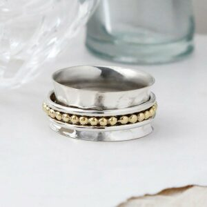 Self care spinner ring on white background, with ripped paper detail and glass vases as background setting