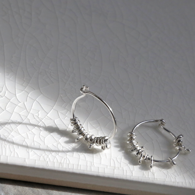 ml918 sterling silver gypsy hoops on white background. one upright.