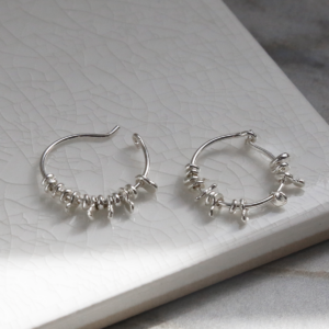 Sterling silver gypsy hoops on white background. one open and one closed.