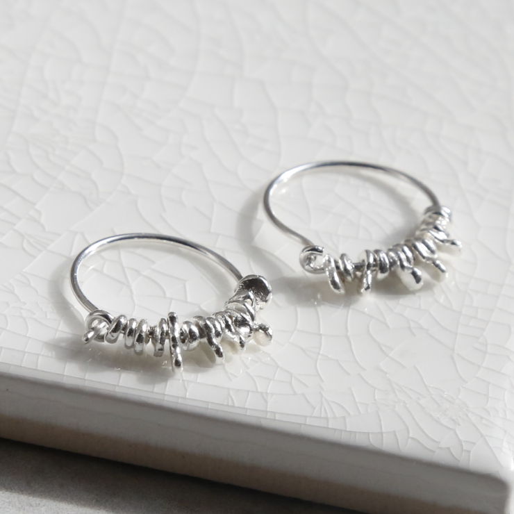 ml918 sterling silver gypsy hoops on white background.  Coin charms catching the light.