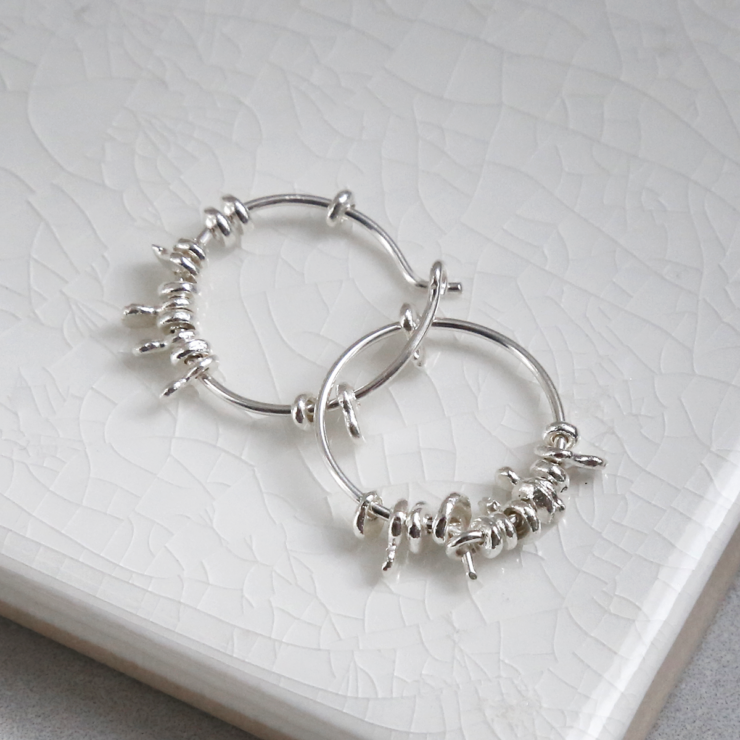 Sterling silver gypsy hoops entwined on white background.