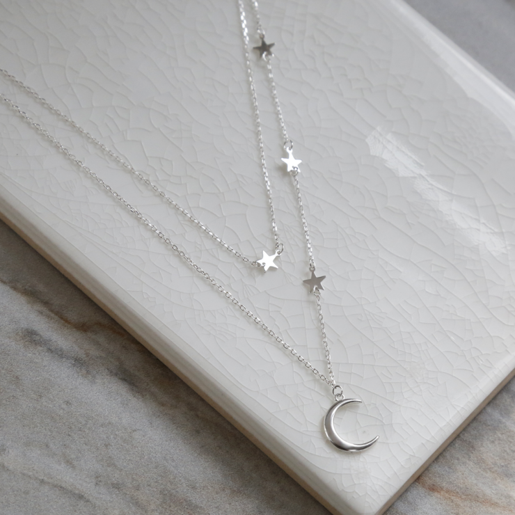Double layered sterling silver moon and star charm necklace on white background.