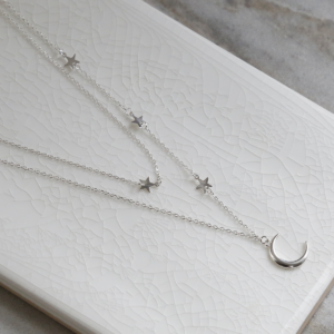 Double layered sterling silver moon and star charm necklace on white background with close up of crescent moon.