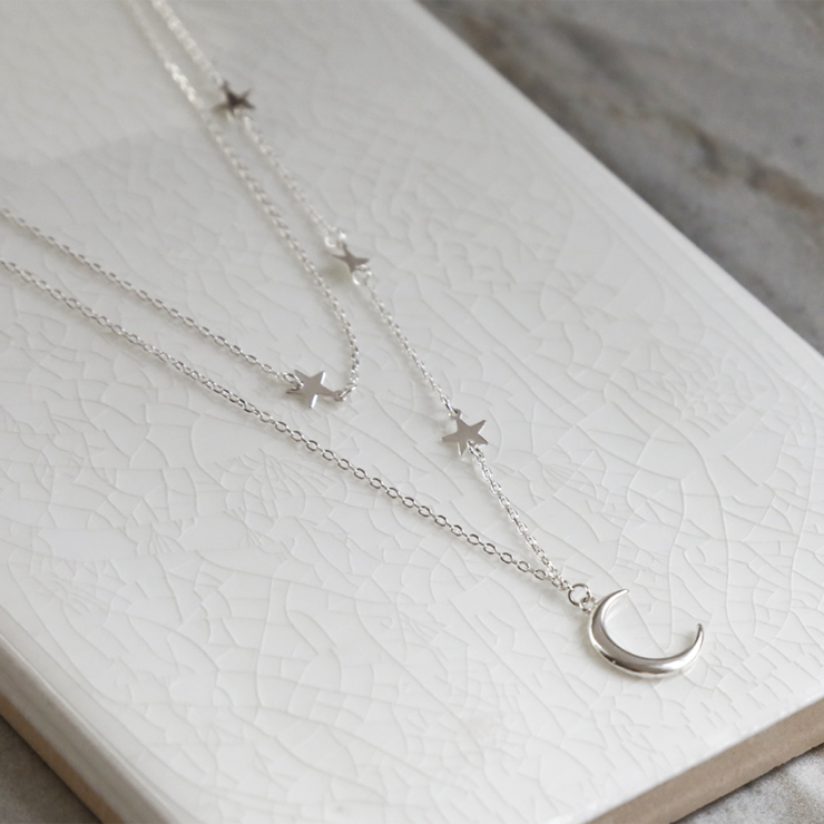 Double layered sterling silver moon and star charm necklace on white background. Close up of stars and moon.
