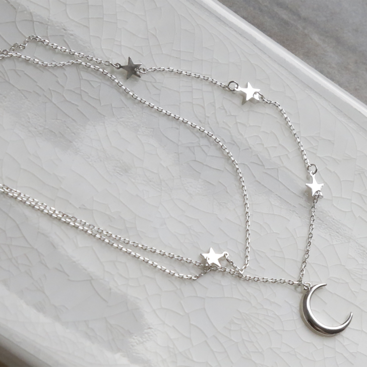 Double layered sterling silver moon and star charm necklace splayed out on white background.