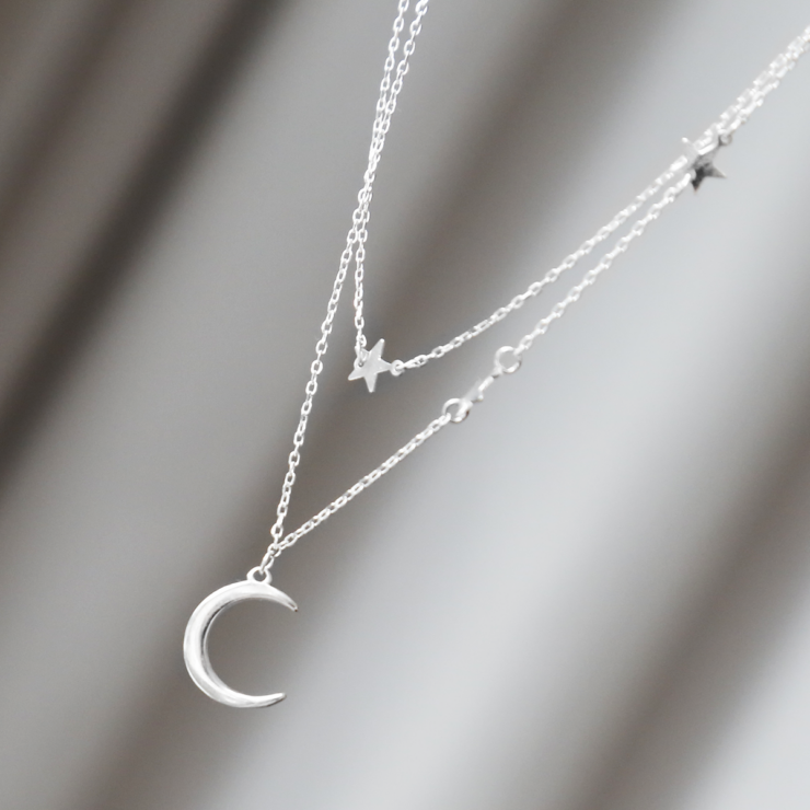 Double layered sterling silver moon and star charm necklace hanging in the air..