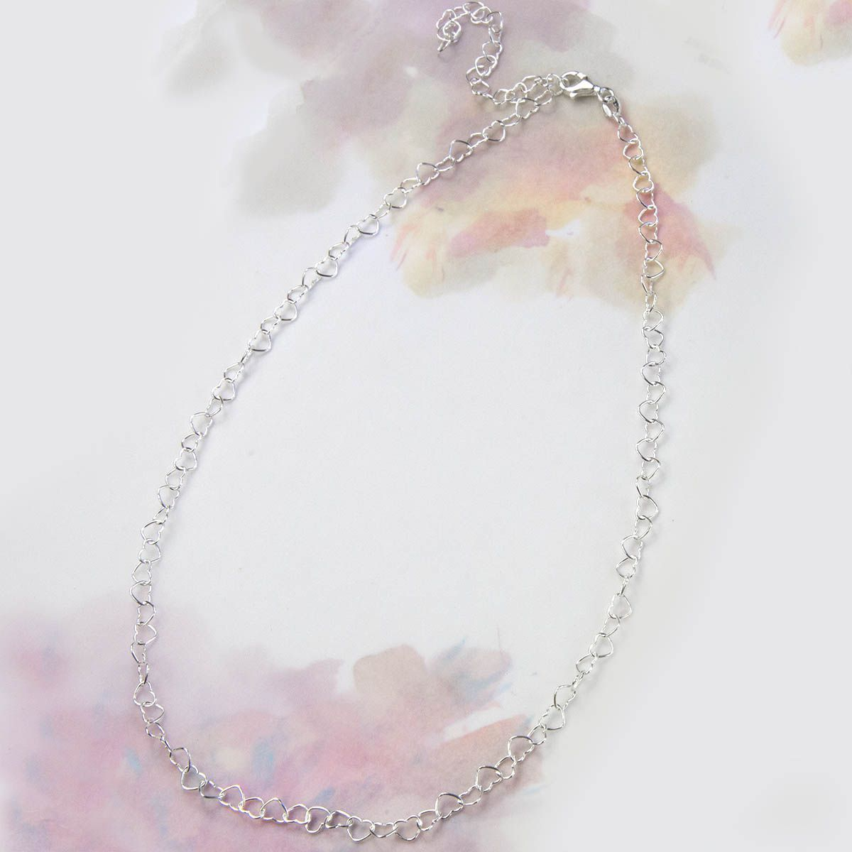 heart shaped wire necklace draped over pink water colour background