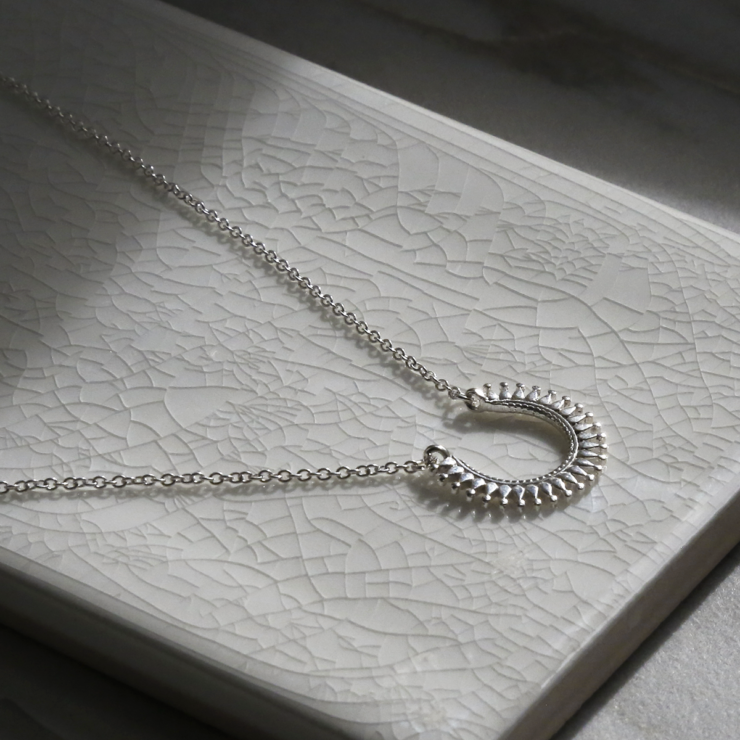 Sterling silver Marrakech horseshoe necklace on white background. Catching the light.